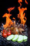 Grilling poultry quails and fresh juicy vegetables in a restaurant Stock Image