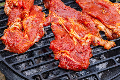 Grilling raw pork steaks on barbecue grill Royalty Free Stock Images