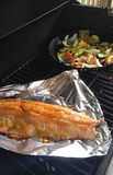 Grilling Salmon and Veggies. Outdoor grill cooking salmon and mixed vegetables Royalty Free Stock Photography