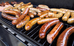 Grilling Sausage. Fresh sausage and hot dogs grilling outdoors on a gas barbeque grill Royalty Free Stock Photo