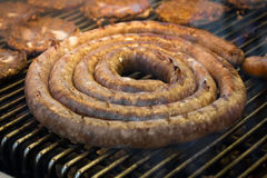 Grilling Sausage Hamburgers. Grilling large juicy sausage with hamburgers for summer barbecue Stock Photos
