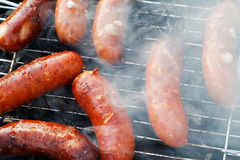 Grilling sausages on barbecue gril Royalty Free Stock Photography