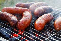 Grilling sausages on barbecue gril Stock Photo