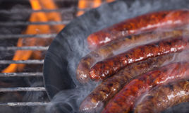 Grilling sausages on barbecue grill. Stock Images