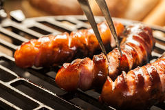 Grilling sausages on barbecue grill Stock Image