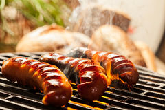 Grilling sausages on barbecue grill Royalty Free Stock Photography
