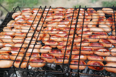 Grilling sausages on barbecue grill. Selective focus Royalty Free Stock Images