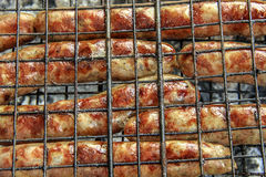 Grilling sausages on barbecue grill. Selective focus Stock Images