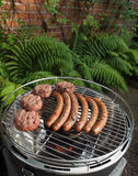 Grilling sausages and beefburgers on a charcoal grill. Sausages and beefburgers cooking on a barbecue in a garden Royalty Free Stock Images