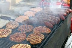 Grilling sausages, burgers, pork steak on barbecues gas grill for party. Hot dogs,sausages and hamburgers on a barbeque, bbq. Smok royalty free stock image