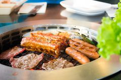 Grilling sausages and meat barbecue on a grill Korean style from the side. Grilling sausages and meat barbecue on a grill Korean style Royalty Free Stock Photography