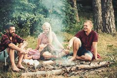 Grilling sausages over campfire, campers roasting sausages on toasting sticks. Fire place with friends or tourists are. Sitting near flame stock photo