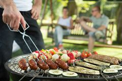 Grilling sausages and vegetables. On bbq party Royalty Free Stock Photo