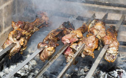 Grilling shashlik on barbecue grill. Royalty Free Stock Images