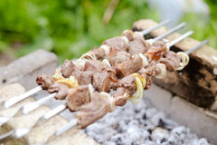 Grilling shashlik with onions on barbecue grill Stock Photo