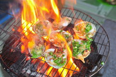 Grilling shellfish and seafood on hot fire Royalty Free Stock Photo
