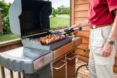 Grilling shish kebob. A man set shish kebob skewers on a grill Royalty Free Stock Photos