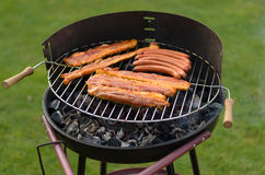 Grilling spicy sausages over a barbecue Royalty Free Stock Photography