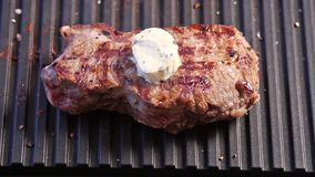 Grilling steak with a piece of butter stock video footage