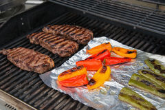 Grilling steaks and peppers Royalty Free Stock Photography