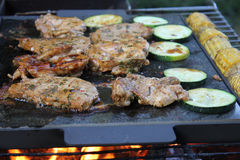Grilling on stone slab. Grilling with barbecue stuff. Meat and vegetables on a stone slab royalty free stock photography