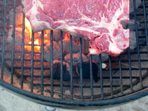 Grilling T-bone steak. Grilling the tip of a T-bone steak on a barbecue griddle over hot glowing charcoal royalty free stock photo