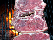 Grilling T-Bone Steaks. Outdoor charcoal grill with t-bone steaks stock images