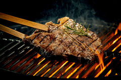 Grilling a tasty tender t-bone steak on the fire Stock Images