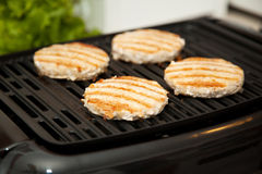 Grilling Turkey Burgers. Healthy, low-fat turkey burgers cooking on indoor grill Stock Photos