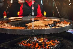 Grilling typical German sausages in a market stall. Christmas market food. Grilling typical German sausages in a Xmas fair in Hamburg stock photography