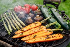 Grilling vegetables with the addition of spices and herbs on the grill plate outdoors. Vegan grilled food, barbecue grill stock photography