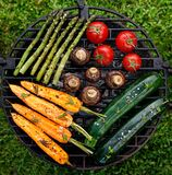 Grilling vegetables with the addition of spices and herbs on the grill plate outdoors, top view. royalty free stock images
