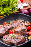 Grillrindfleischsteak Saftige Lendensteaks des starken Rindfleisches der Teile auf Grillteflonwanne oder altem hölzernem Brett Lizenzfreies Stockbild