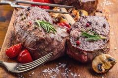 Grillrindfleischsteak Saftige Lendensteaks des starken Rindfleisches der Teile auf Grillteflonwanne oder altem hölzernem Brett Stockbilder