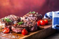 Grillrindfleischsteak Saftige Lendensteaks des starken Rindfleisches der Teile auf Grillteflonwanne oder altem hölzernem Brett Lizenzfreie Stockbilder