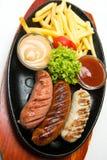 Grillworsten op de houten plaat met frieten en sausen Witte achtergrond Stock Afbeelding