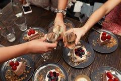 Grils党 Grils欢呼玻璃用香槟在餐馆 点心蛋糕背景 库存照片