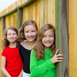 Grils group in a row smiling in a wooden fence. Outdoor Royalty Free Stock Photos