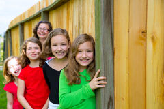 Grils group in a row smiling in a wooden fence. Outdoor Stock Image