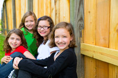 Grils group in a row smiling in a wooden fence. Outdoor Royalty Free Stock Image