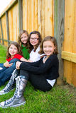 Grils group in a row smiling in a wooden fence. Grils group in a row smiling sitting in a wooden fence outdoor Royalty Free Stock Photo