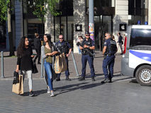 Grils shopping and policemen guarding the road. Lille, France - May 26, 2017: Girls walk by with shopping bags while police officers with guns guard a roadblock Royalty Free Stock Image