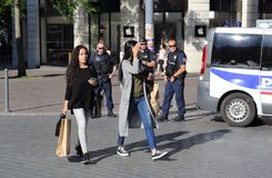 Grils shopping and policemen guarding the road. Lille, France - May 26, 2017: Girls walk by with shopping bags while police officers with guns guard a roadblock Stock Image