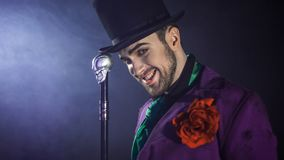 A grim circus presenter, a demonic smile. Image on Halloween. The guy in the purple camisole and the cylinder. Bright tailcoat, suit Royalty Free Stock Images