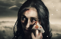 Grim face of horror crying tears of blood. Fine art horror photo of a zombie woman crying tears of blood in a cold winter storm when expressing the sadness of Royalty Free Stock Photography