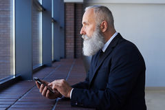 Grim male looking out window while working in phone Royalty Free Stock Image