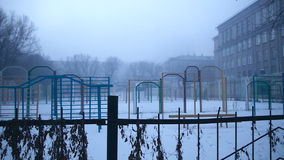 Grim playground in the mist of the old school. On winter day stock video