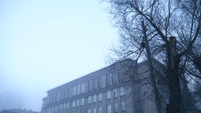 Grim playground in the mist of the old school. On winter day stock video footage