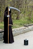 Grim reaper. Street entertainer, grim reaper figure. The death with a scythe, a box in front of him to collect money gifts Royalty Free Stock Photo