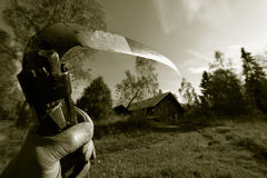 Grim reaper on the move. Gloved hand holding old scythe on the way to old farm-house, reaper idea. and in brown toning, focal-point on blade Royalty Free Stock Photography